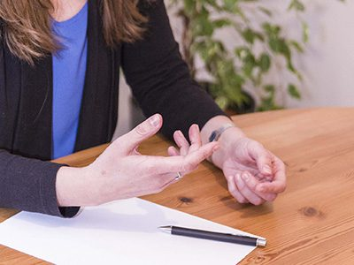 Person am Tisch mit Zettel und Stift